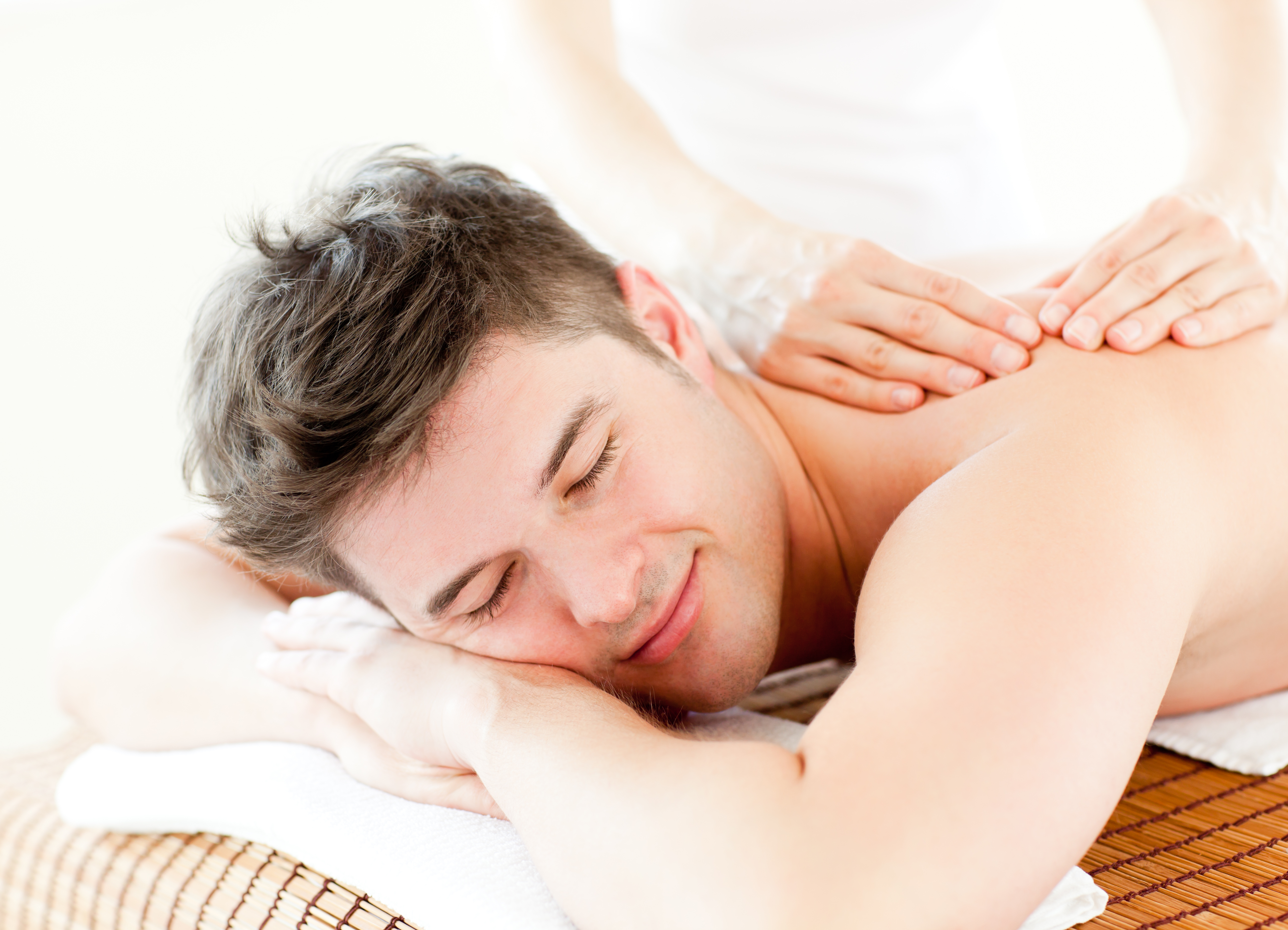 Relaxed young man receiving a back massage in a spa center